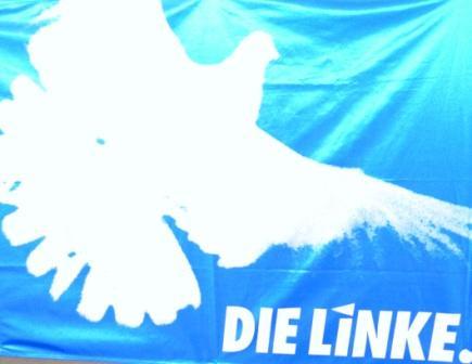 Blaue Fahne mit weißer Friedenstaube und weißer Aufschrift. Foto: Eckart Kreitlow