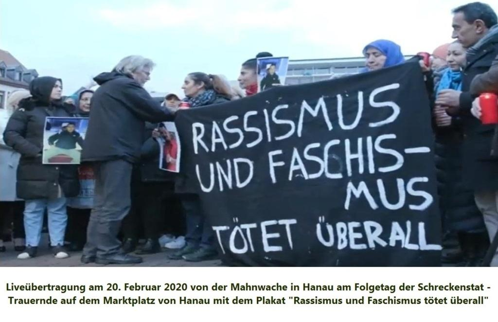 Liveübertragung am 20. Februar 2020 von der Mahnwache in Hanau am Folgetag der Schreckenstat - Trauernde auf dem Marktplatz von Hanau mit dem Plakat 'Rassismus und Faschismus tötet überall!'